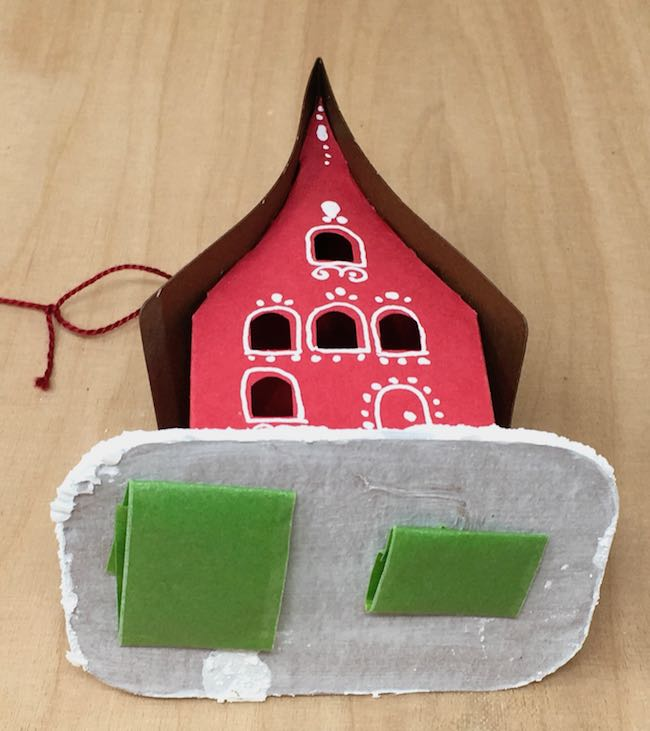 Adhere the paper house ornament to the box with painters tape