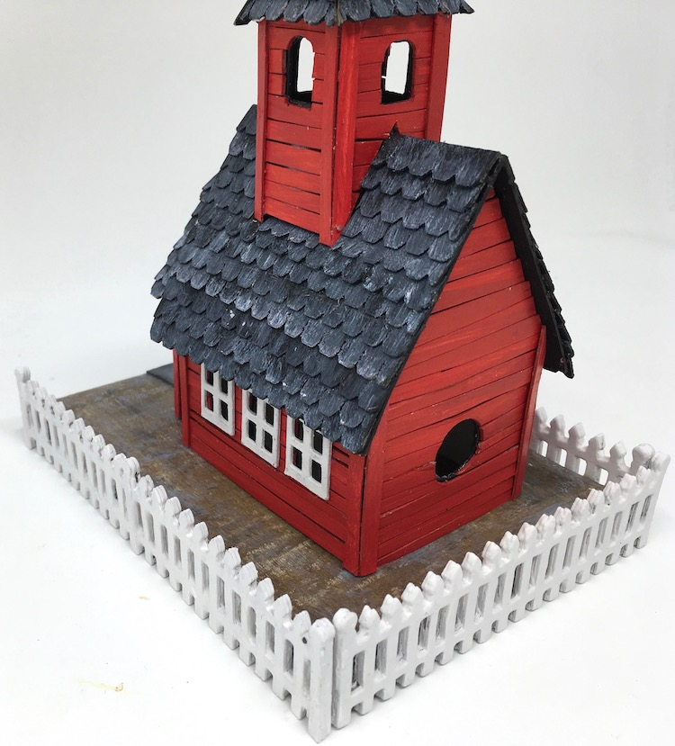 Back of red schoolhouse little paper house showing cardboard fencing
