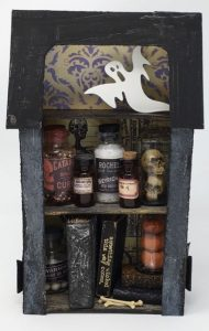 Apothecary diorama with medicinal vials and bottles, miniature spell books on the bottom shelf and a ghost haunting the attic