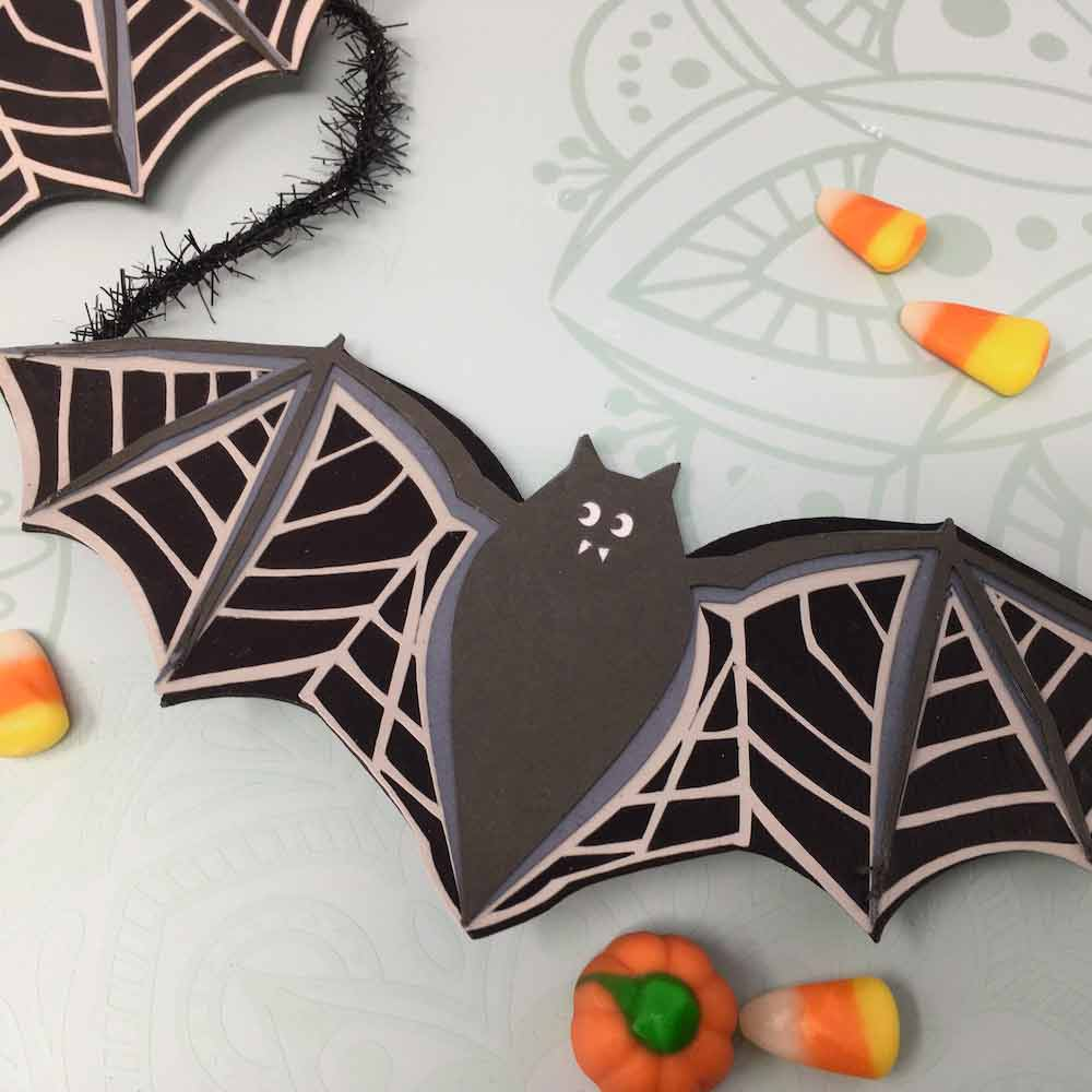 Bat garland made of layered cardstock with halloween candy around