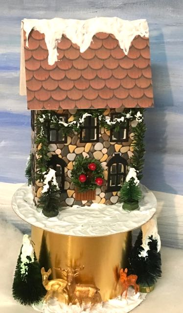 Beautiful little Putz house with stone siding, ribbon roll base, garland around the house