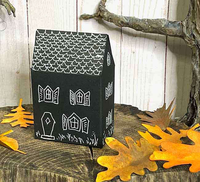 Black cardstock haunted cottage treat box with paper leaves around