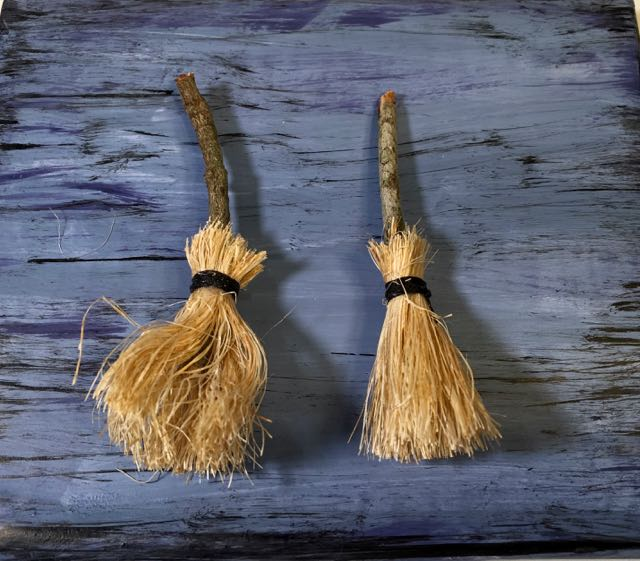 Tiny handmade DIY brooms on blue background