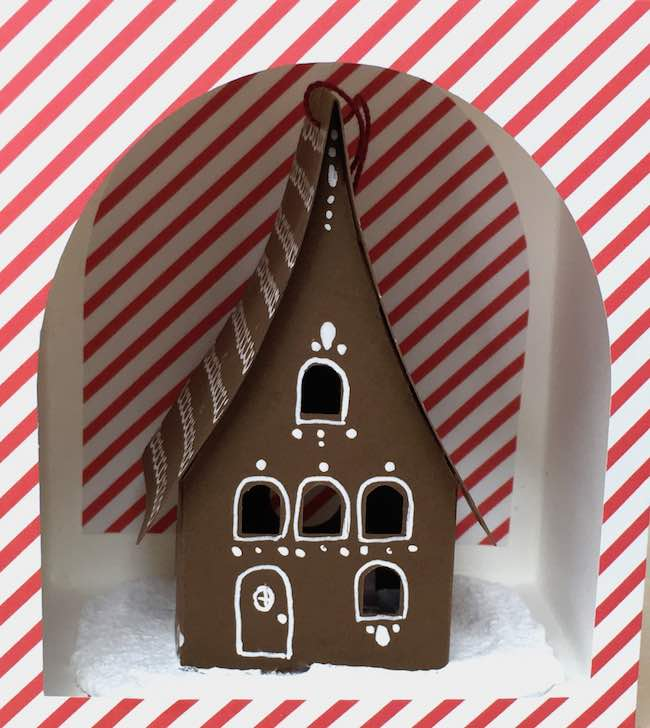 Brown gingerbread paper house ornament in candy stripe paper