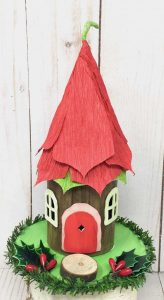 Christmas fairy house with poinsettia flower on roof