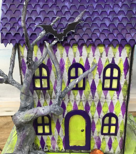 Close-up front view of Harlequin House with stenciled diamonds, twisted tree