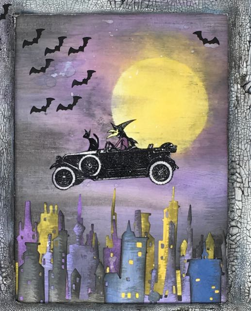 Stamped, embossed image of the witch driving her vintage auto on a Halloween wall hanging