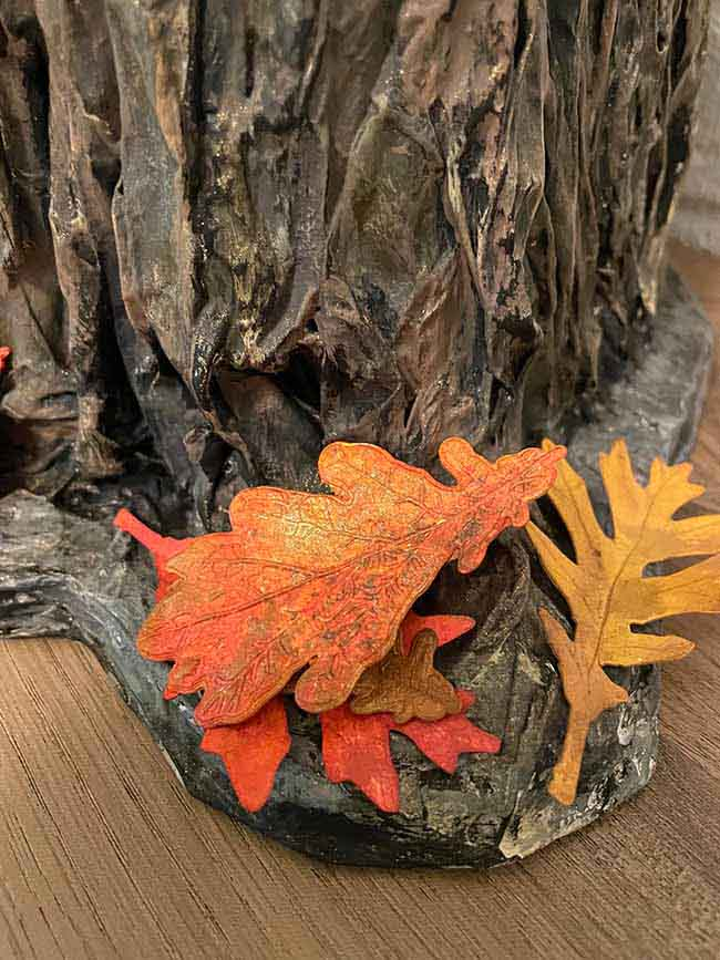Colorful paper leaves at base of paper mache tree stump