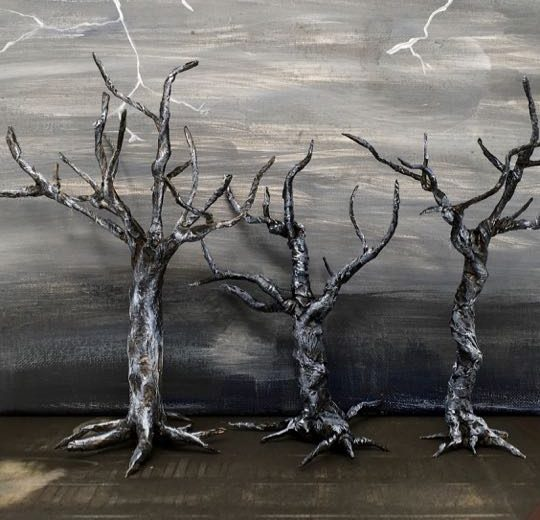 3 spooky twisted trees in front a grey painted stormy background