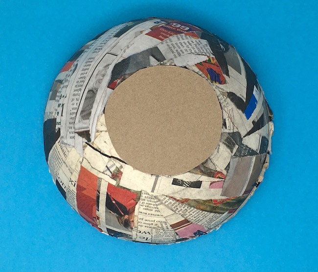 Cut cardboard to fit the hole on bottom of paper mache egg