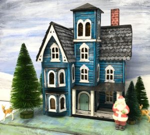 The Faded Mansion cardboard house is dressed for Christmas season bottlebrush trees, santa and deer