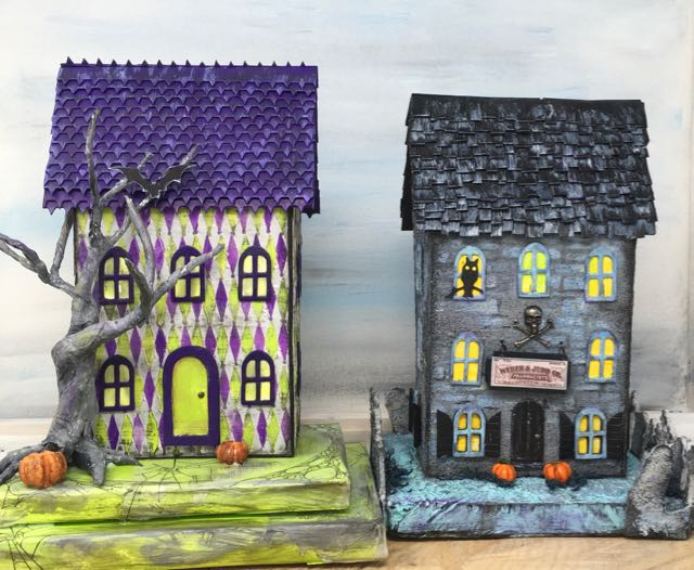 Two miniature Halloween houses with an open back decorated with spooky Halloween decor