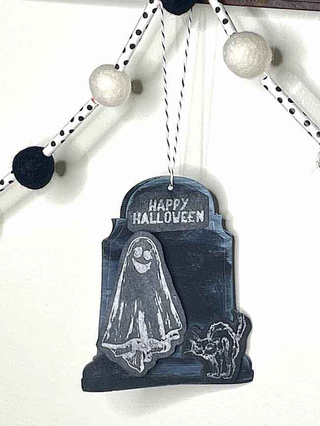 Ghost and kitty Halloween ornament on black cardstock hanging from garland