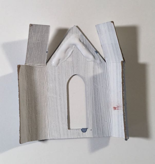 Glue those roof flaps down on snowy church paper christmas house