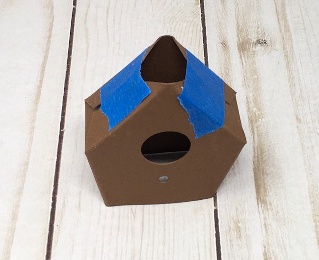 Glue roof tabs to roof flaps on paper birdhouse