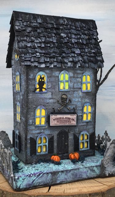 Front view of the Apothecary Halloween House with an owl in an upper window, pumpkins by the front door, moss around the pumpkins
