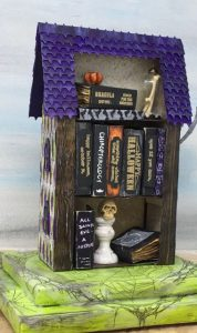 Books titles and specimen jars on the back of miniature Harlequin House Used Bookstore #putzhouse #halloweenhouse #papercraft
