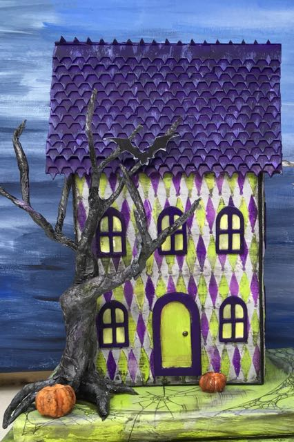 Bendable wire roots on the Harlequin Halloween House extend over the base