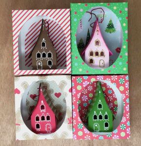 Holiday paper house ornaments in display boxes