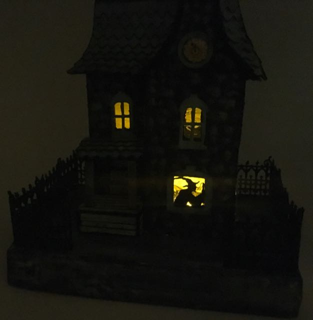 paper house lit up inside to show witch
