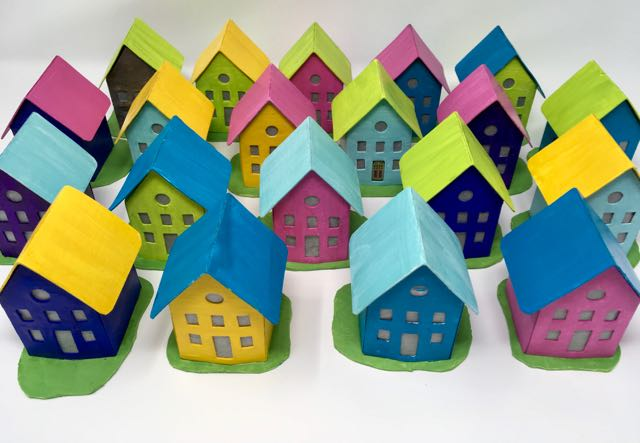 Little paper houses all in a row ready to be packed for a trip