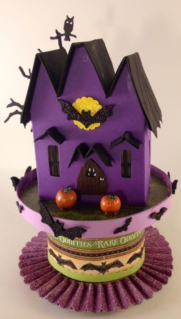 Bat Wing Halloween house made with a ribbon roll base with lots of bats flying around #halloweenhouse #putzhouse #halloween #papercraft