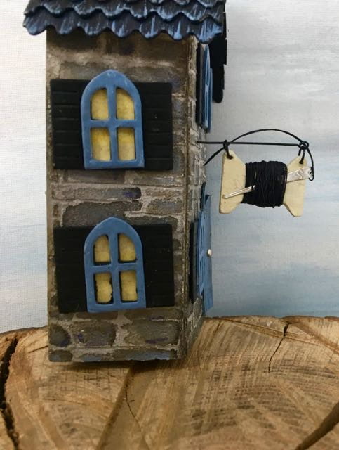 Side view showing the needle and thread sign in place on the miniature Halloween Haberdashery