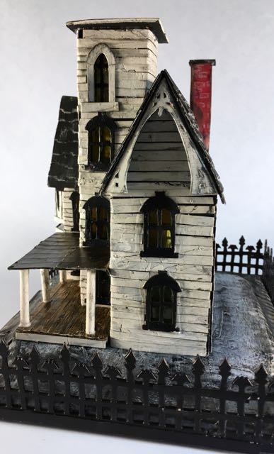 Italianate Halloween House porch side view. Yes, hand cut trim around that gable too. #halloweenhouse #halloween #putzhouse #papercraft
