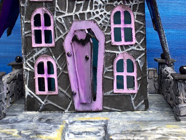 Reinforced the Coffin-shaped door on the Bat Wing Halloween Paper house with bookbinder's tape #halloweenhouse #putzhouse #halloween #papercraft