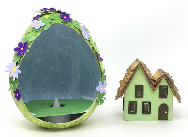 Inside paper mache egg painted with stormy sky paint beside miniature Irish cottage