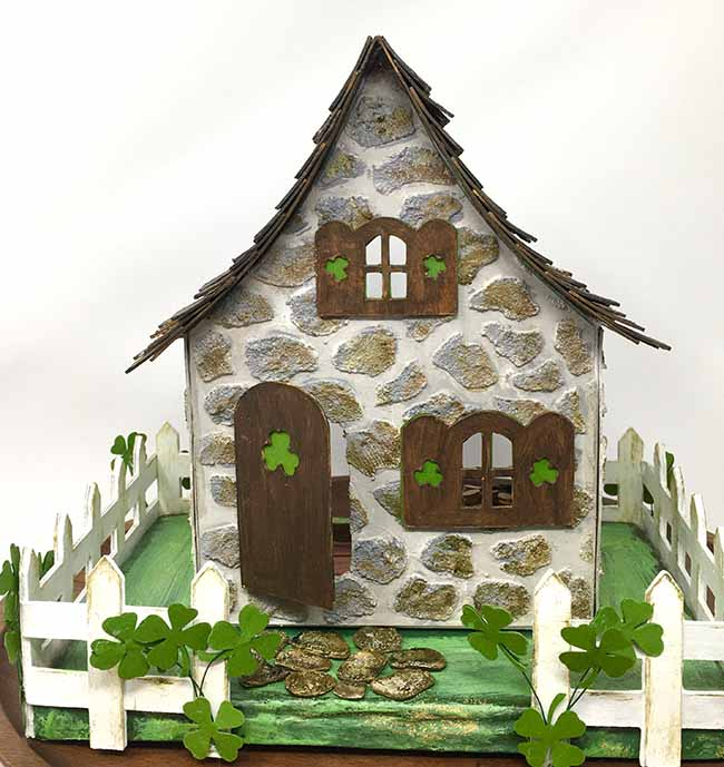 Leprechaun house made from cardboard adorned with shamrocks and gold glitter