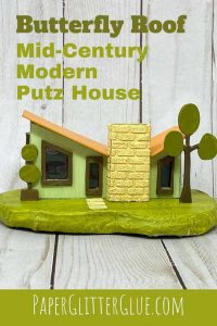 Butterfly Roof Mid-Century Modern Putz house with yellow chimney in front retro trees on each side