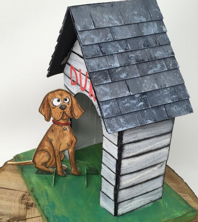 Staggered shingles on miniature cardboard doghouse