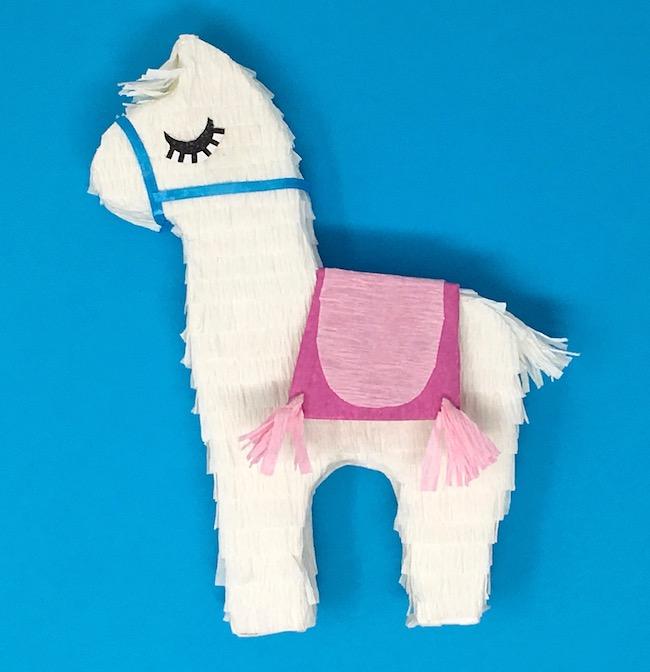 Mini llama piñata decorated with pink saddle blue bridle