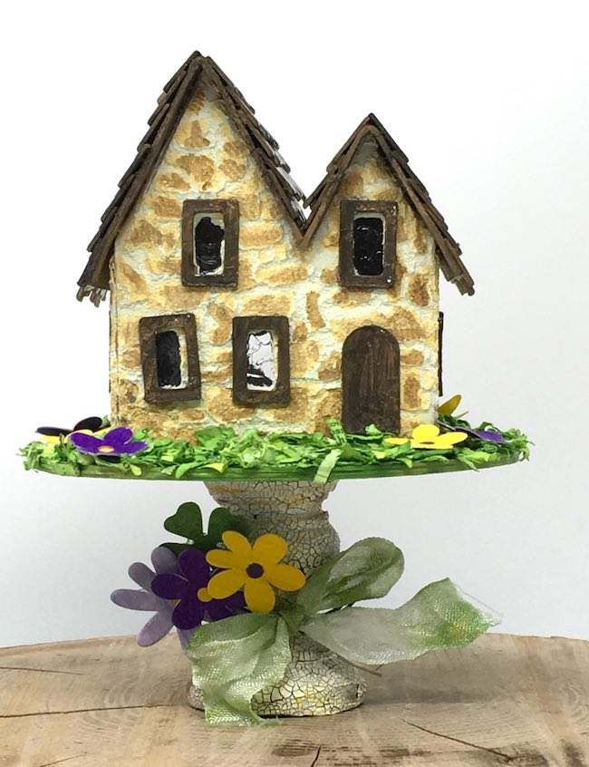 Miniature Irish Stone Cottage putz house for St. Patrick's day with pedestal base covered with paper flowers