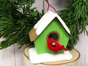 Miniature paper birdhouse with cardinal