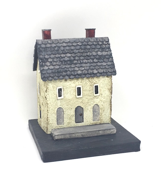 Miniature plaster house covered with fine stone granules