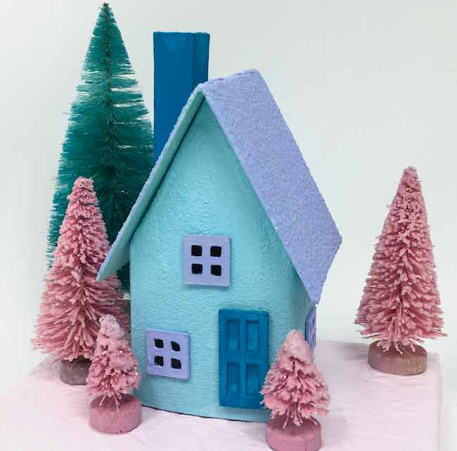 Tiny blue paper house with pink bottlebrush trees