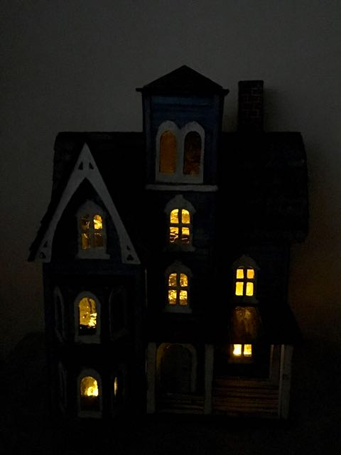 Photo of little putz house in dark with lights on