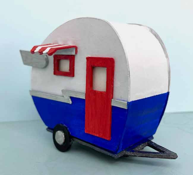 side view of tiny paper RV trailer painted in red white and blue