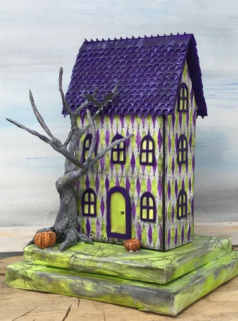 Right side view showing the twisted tree and pumpkins on the front of the miniature Halloween bookstore