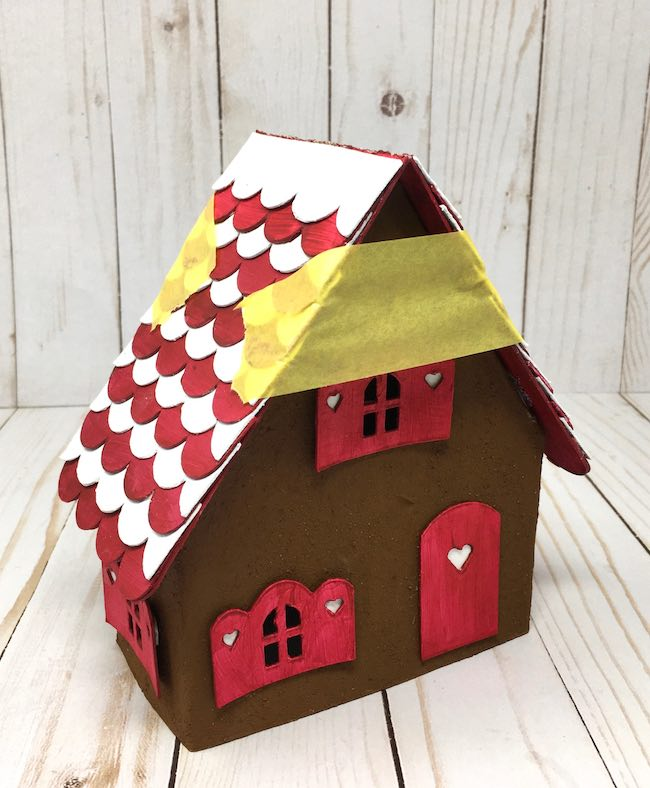 Roof piece held onto gingerbread house with painters tape