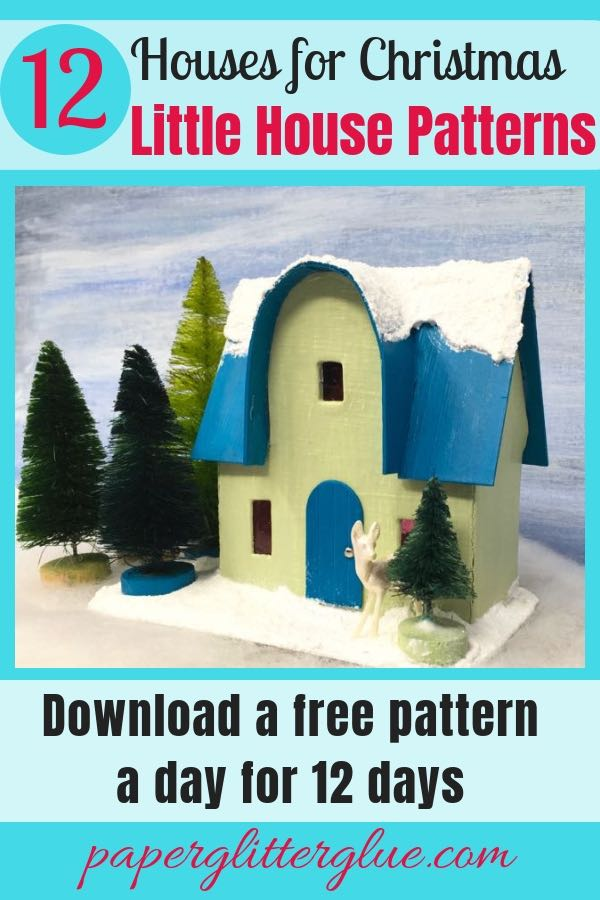 Miniature Christmas paper house with a glittered, snowy roof and a forest of bottlebrush trees