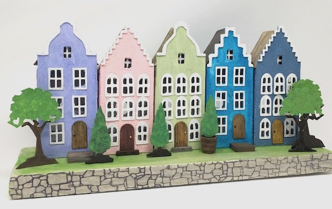 Row of paper houses Dutch canal house facades on cardboard base