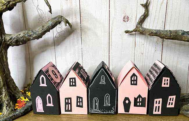 Row of pink and black cardstock Halloween house gift boxes