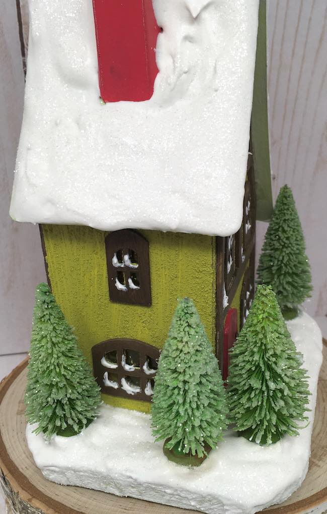 Snowy roof on storybook cottage chimney side