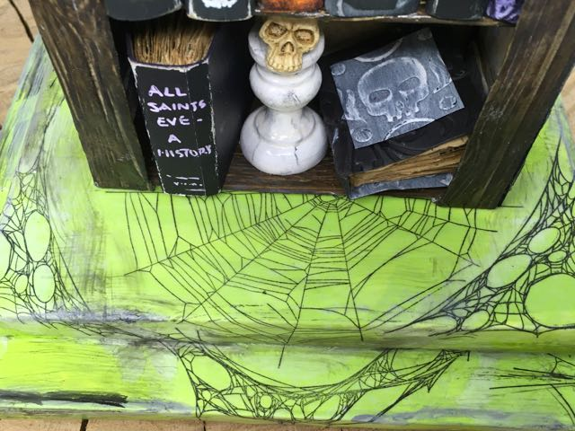 Spider webs decorating the cardboard base of the miniature Halloween bookstore #timholtz #stampersanonymous #putzhouse #papercraft
