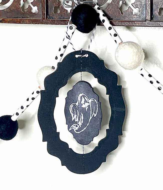 Spinning ghost chalkboard Halloween ornament hanging from felt ball garland