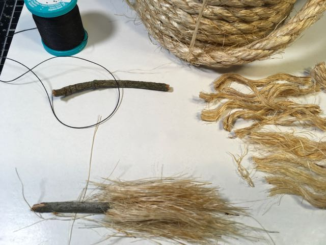 Layer the uncoiled sisal on your tiny broomstick twigs.