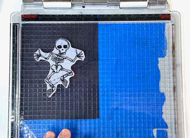 Stamp dancing skeleton on black cardstock